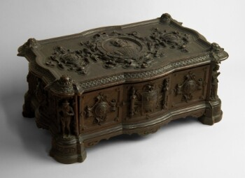 A wooden box with a hinged lid, varnished to a dark mahogany colour. The surfaces have decorative carvings. In each corner, a figure representing a character from Shakespeare's plays stands in an alcove. On the side of the box facing the viewer, a coat of arms is carved on the centre panel, with medallions either side embossed with Shakespeare's entwined initials. On the lid, a portrait of Shakespeare in a decorative oval in the centre is flanked by two smaller shields carved with his birth date of 23 April 1564 and death date of 23 April 1616.