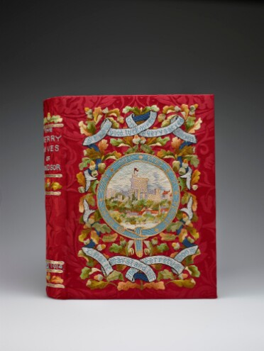 A book with a colourful embroidered cover. The background is a red brocade silk. At the centre of the cover a round view of Windsor Castle is framed by the blue ribbon of the Order of the Garter, embroidered with its motto 'Honi soit qui mal y sense.' Above and below are further ribbons bearing quotes from the play ('Strew good luck ouphes in every sacred room/ That it may stand till the perpetual doom'), strung across a backdrop of oak leaves and acorns. On the book's spine, the title 'The Merry Wives of Windsor' can be seen embroidered in blue thread, and the date A.D. 1914, with further oak leaf and acorn motifs.