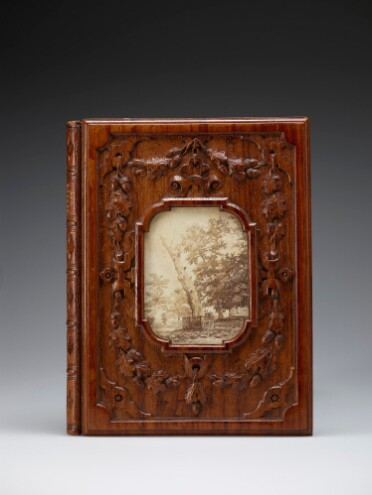 The front cover of a book with a wooden binding. The wood is varnished to a dark reddish brown, and carved with oak leaves and acorns. The title 'Herne's Oak' is just visible embossed on the spine. In the centre, a cutaway section in the wooden cover reveals a sepia photograph of an old, dying oak tree with a fence around its base, with other, living trees in the background.
